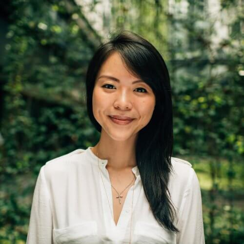 Long black haired and black eyed asian woman wearing a white shirt and a cross necklace with a nature background