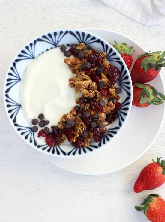 Blue bowl of Mocha Latte Vanilla Granola on yoghurt next to fresh strawberries