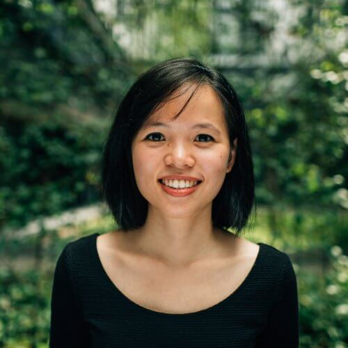 Short black haired and black eyed asian woman wearing black with a nature background