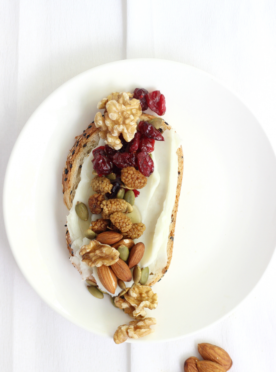Berry-licious nut mix with cranberries, walnuts, mulberries, pepita seed and almonds on cream spread on a slice of bread