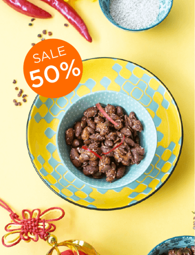 Top down shot of Miso Szechuan Nut Mix in blue bowl on yellow background with 50% Sale messaging