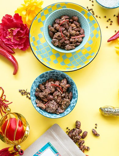 Top shot of Miso Szechuan Nut Mix in small bowl on yellow background