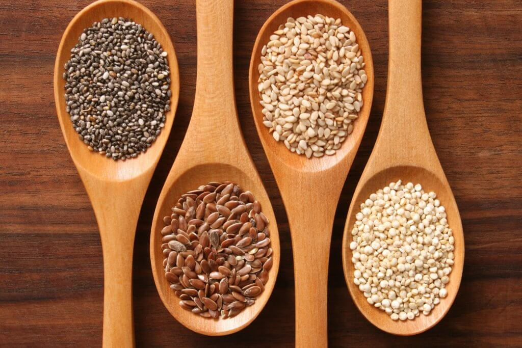 What's in my granola - Wooden spoons with chia seeds, flax seeds, sesame seeds, and quinoa